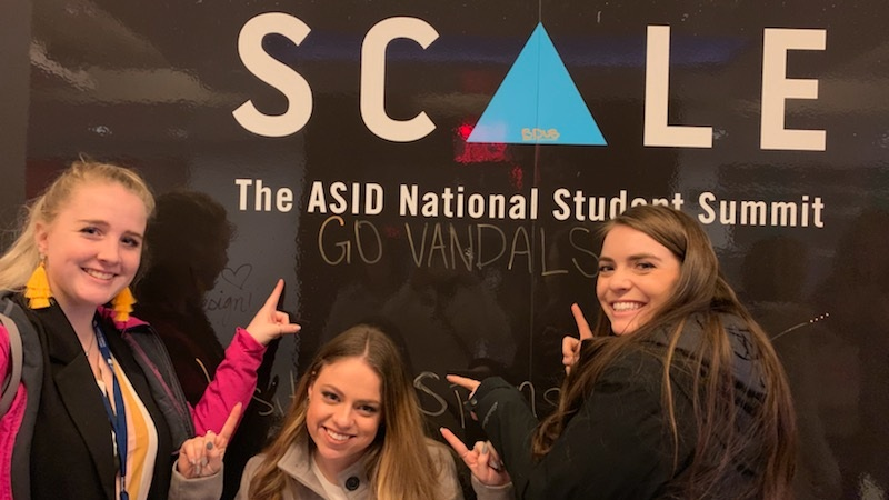 Three students pose in front of an event poster at the ASID National Student Summit.