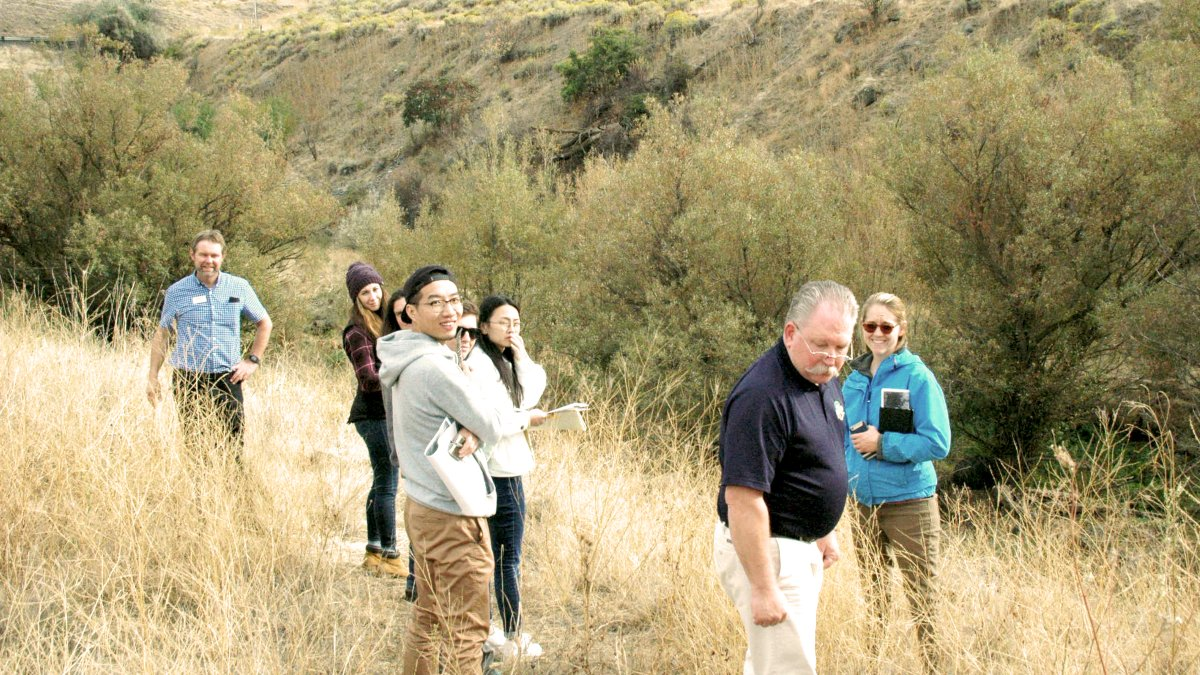 Students and faculty stand in a group in an area of wild grass with hills rising behind them.