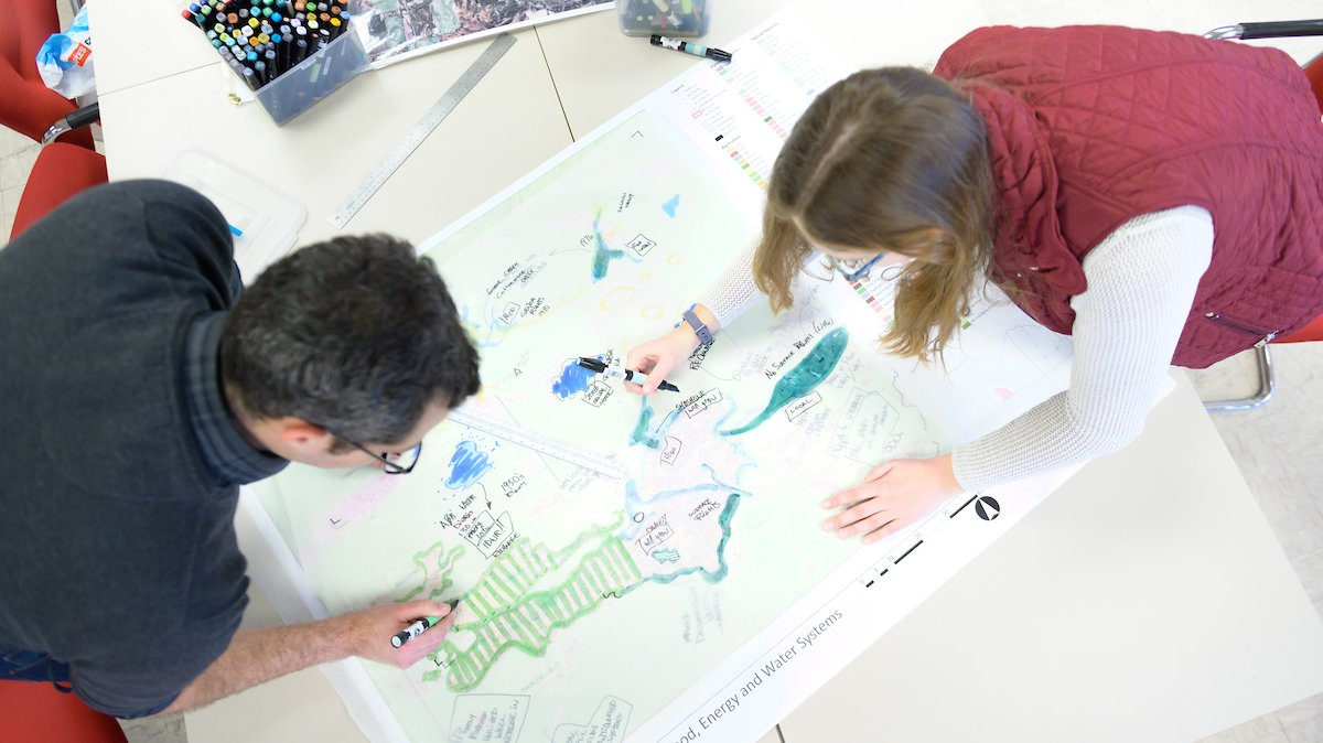 A view from above of two INFEWS researchers working on a large drawing with colored markers.
