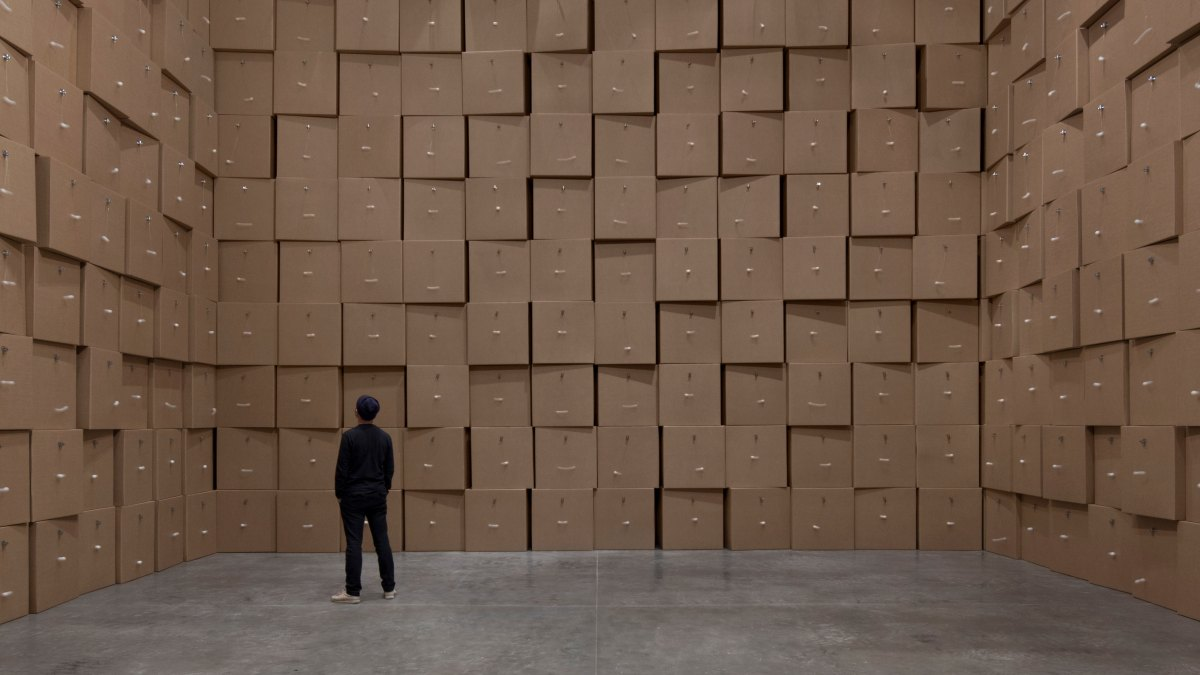 A man observes a Zimoun installation resembling a wall of cardboard boxes.