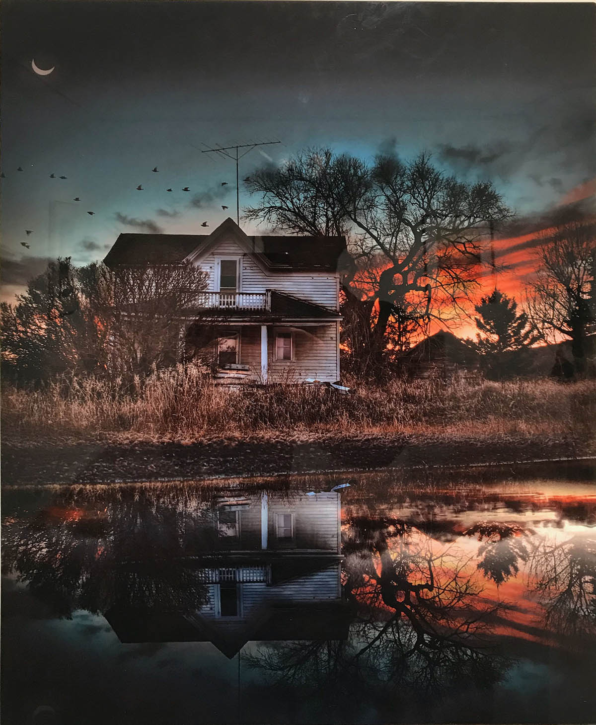 Photograph of an abandoned house in a rural area with an orange sunset behind it.