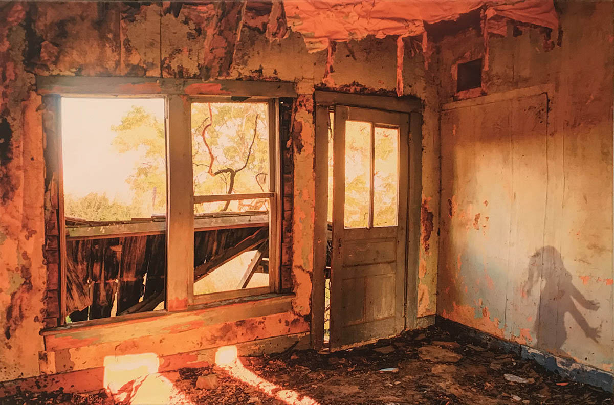 Photograph of a room inside an abandoned house. A young girl's shadow is appears on a wall.
