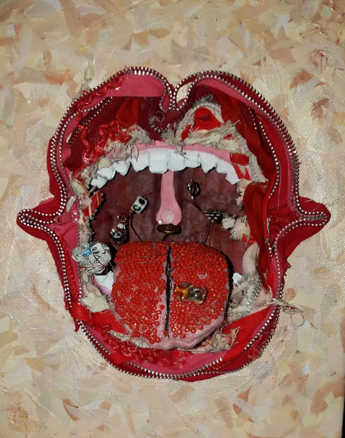 Sculpture of an open mouth made from found objects, including a zipper, fabric and beads.