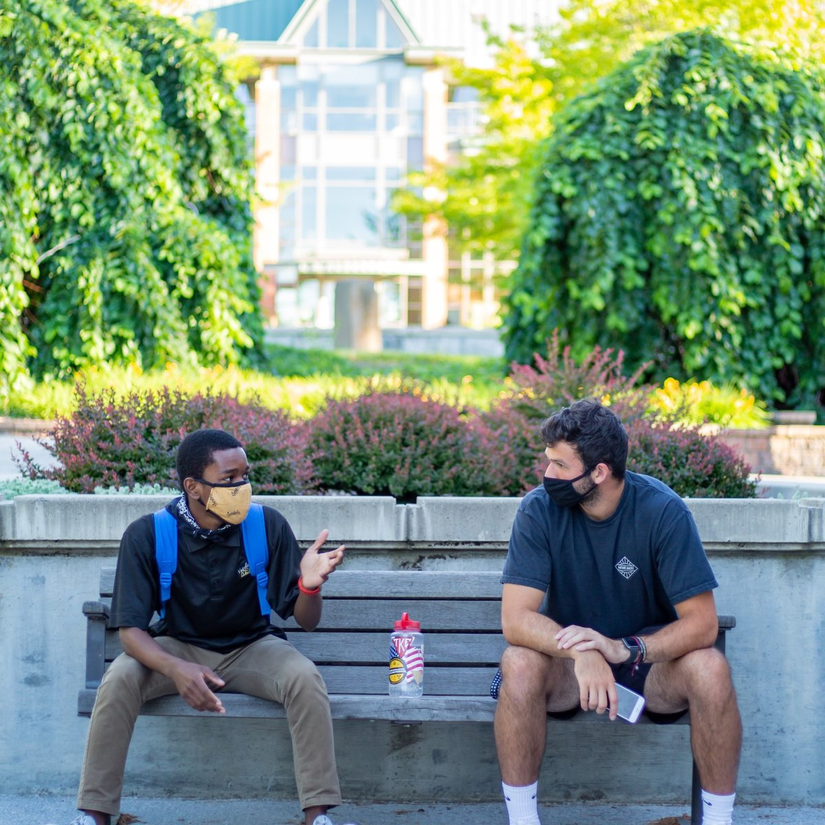 Two students wearing Vandal-themed face coverings enjoy a conversation on a bench outside the J.A. Albertson building.