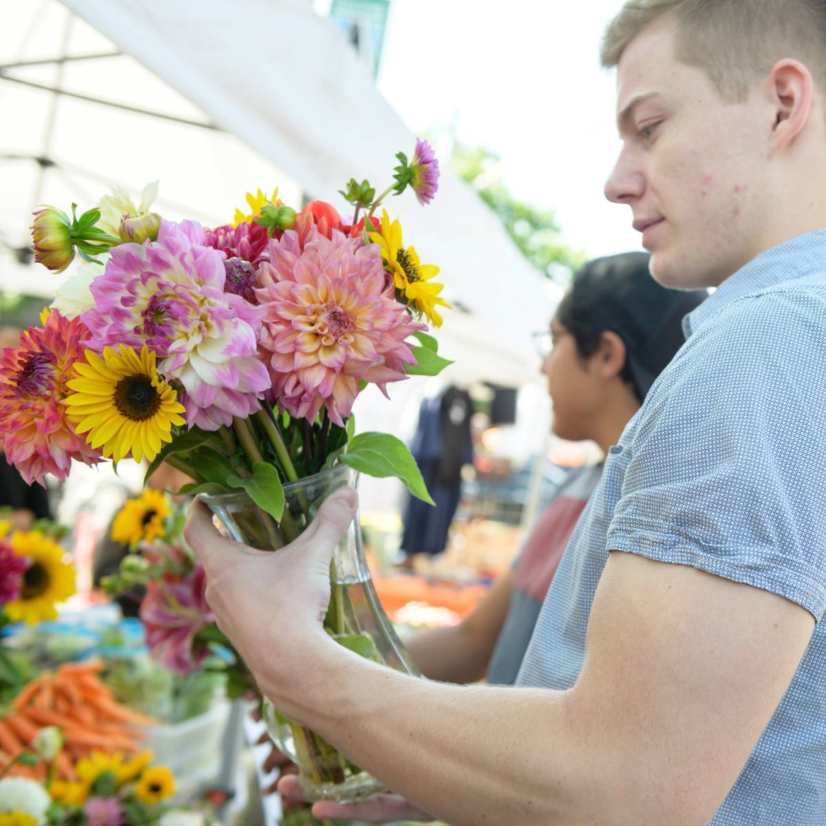 A man holds brightly colored flowers.