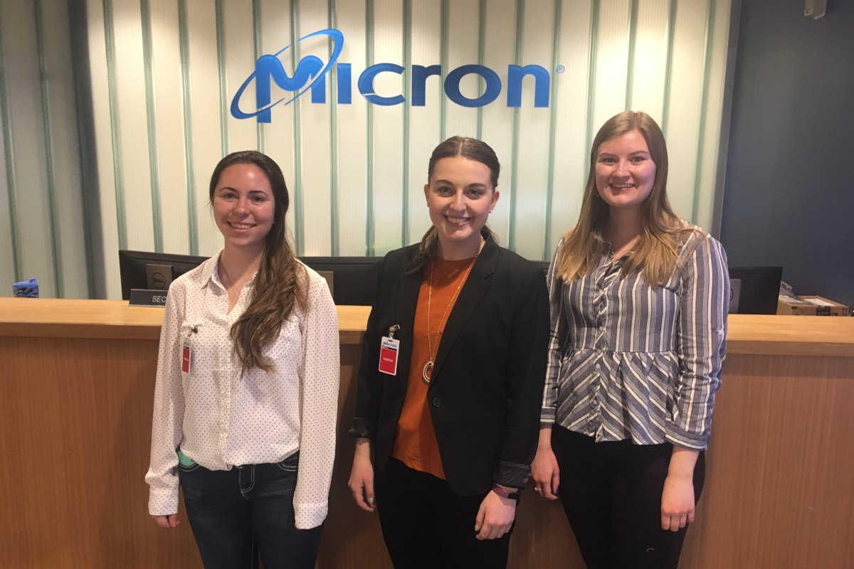 Morgan Hughes, Hayley Parks and Kaarin Von Bargen stand in front of a Micron logo mounted on the wall.