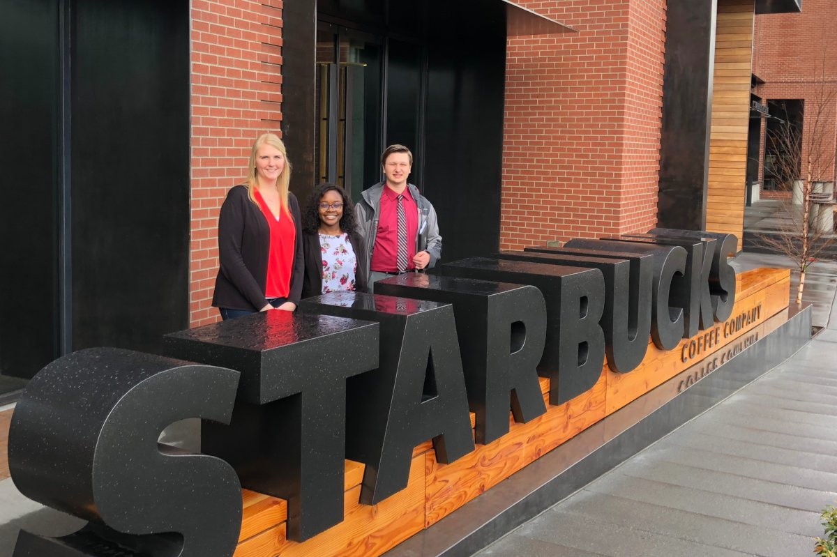 Oluwadamilola Olape and Ryan Zimmerman pose with Starbucks executive Emily Marks in front of the Starbucks building in Seattle.