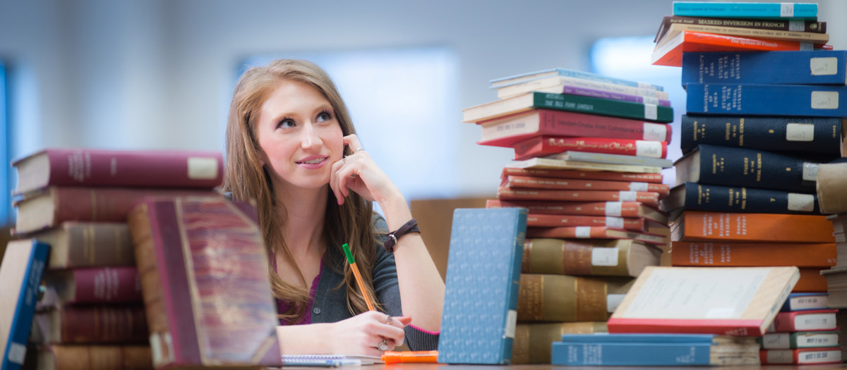A student surrounded by books in the library.