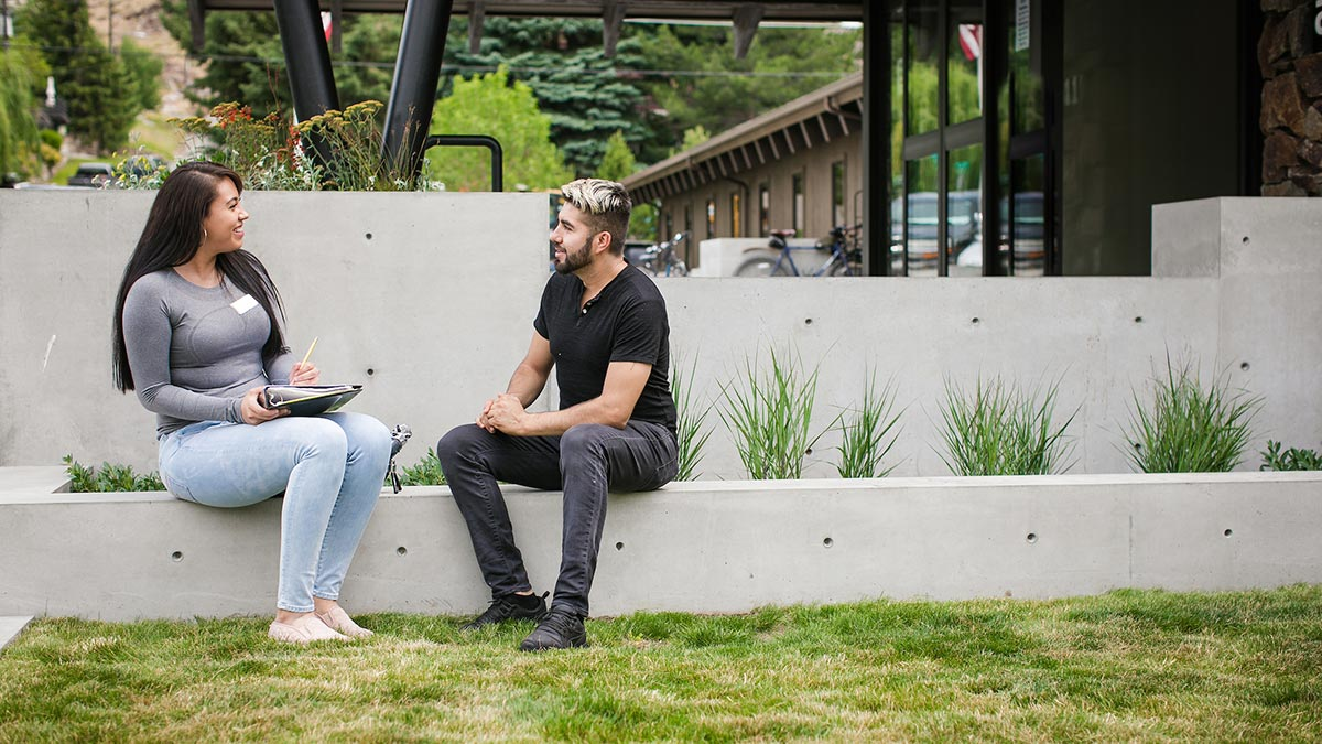 Gisele Andrade talking outdoors with a young man.