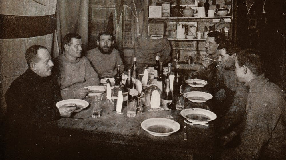 Six members of Robert Falcon Scott's Terra Nova Expedition gather around a table for a meal in 1912.