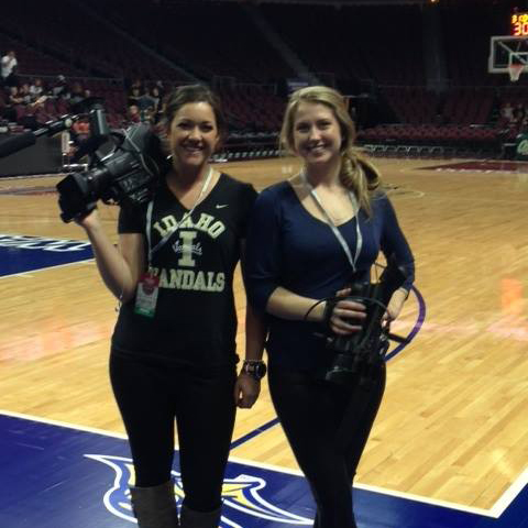 Two students with cameras on the basketball court before a game