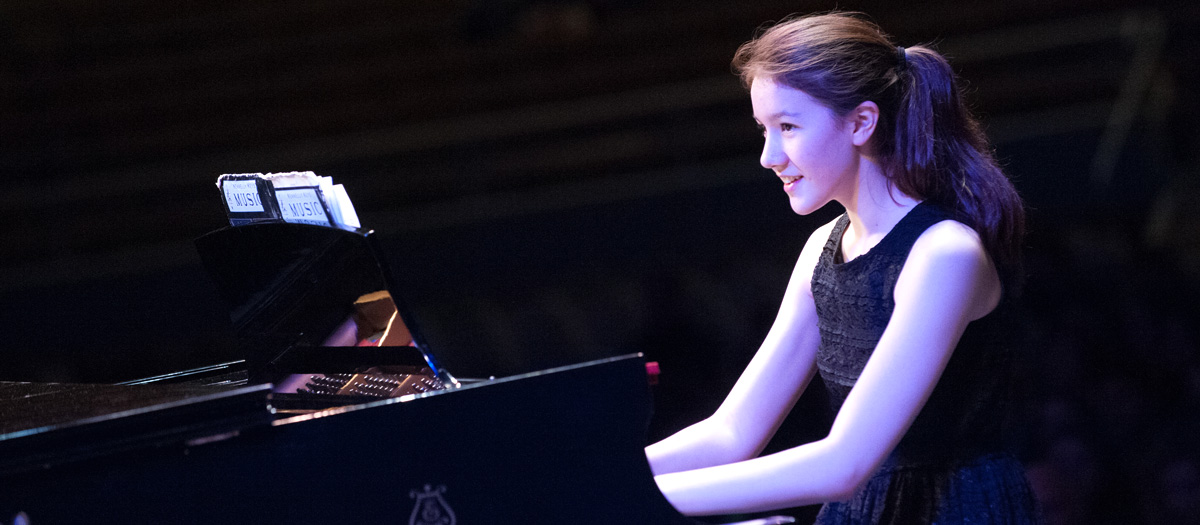 Student plays the piano onstage
