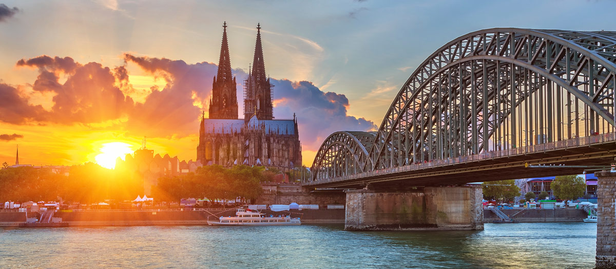 A bridge and church in Cologne at sunset.