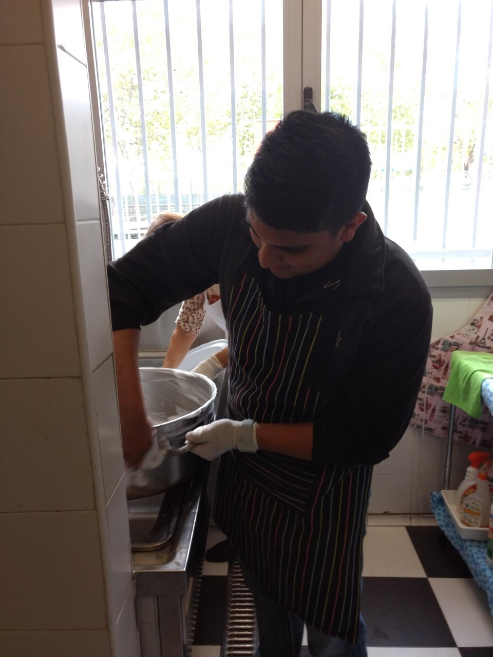 Ramon Juarez washes dishes in a soup kitchen in Madrid