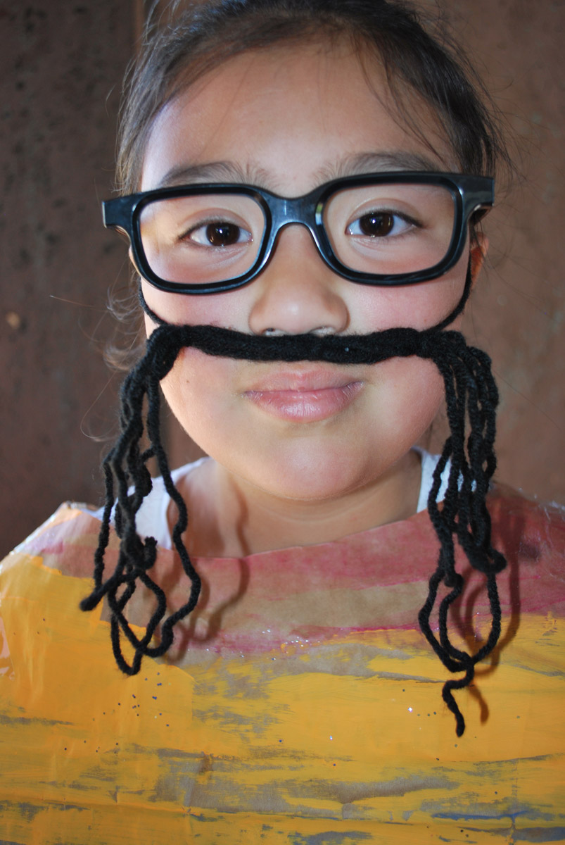 A child in costume with a yarn mustache.
