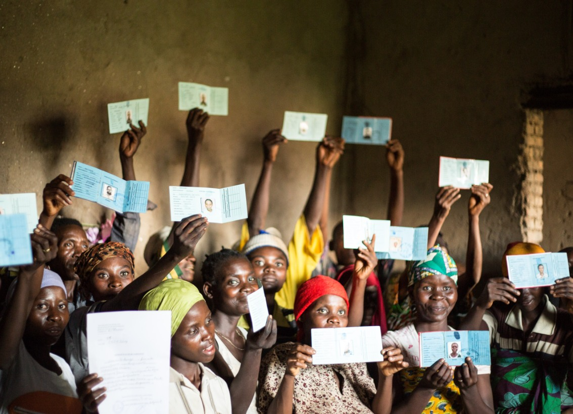 A group of African women hold up their new ID cards
