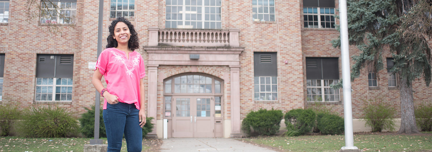 Luz Anaheli Stegner stands in front of school building.