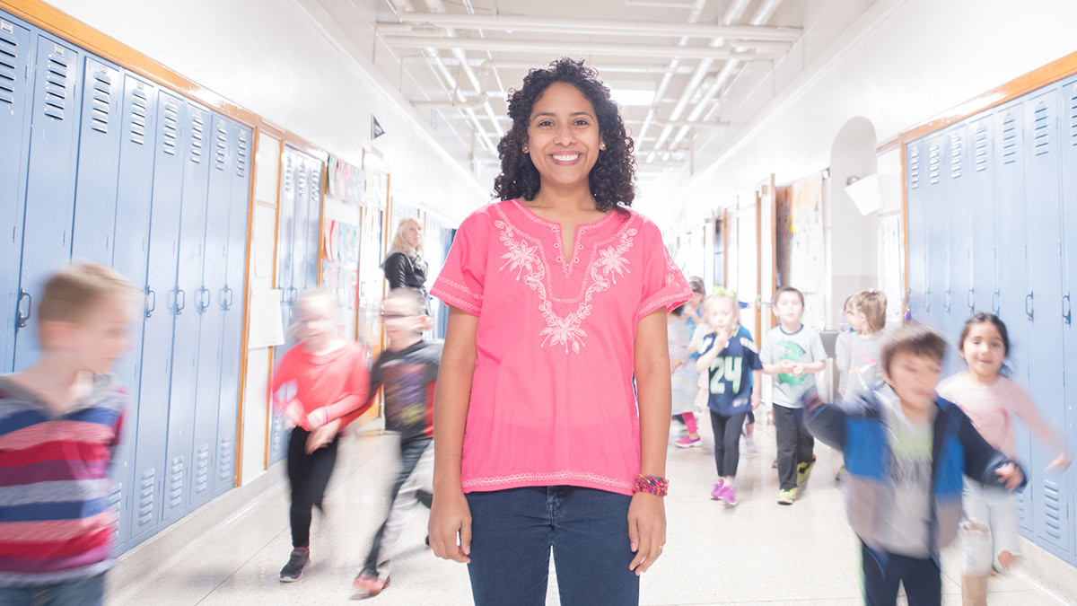 Luz Anaheli Stegner stands in hallway of elementary school building.