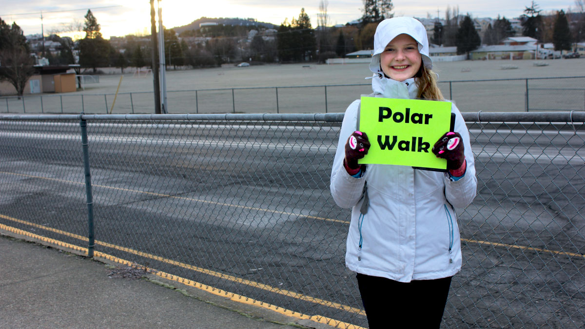 Girl in coat and gloves holding Polar Walk sign
