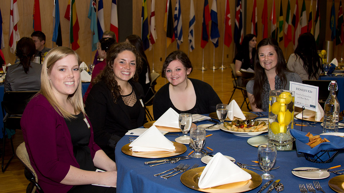 Students sit at tables before meal service begins at the Dine With Style Etiquette Dinner.