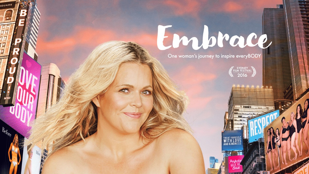activist Taryn posed in front of a city with billboards and the title of the movie: Embrace in text