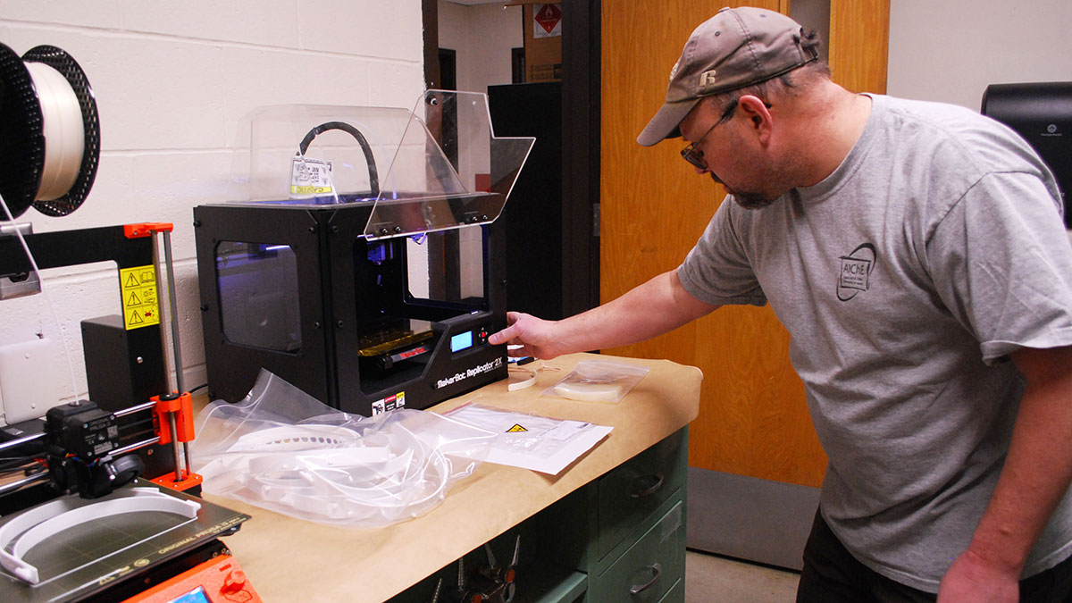Scientific Instrument Maker Charles Cornwall adjusts a 3D printer to complete a face shield.