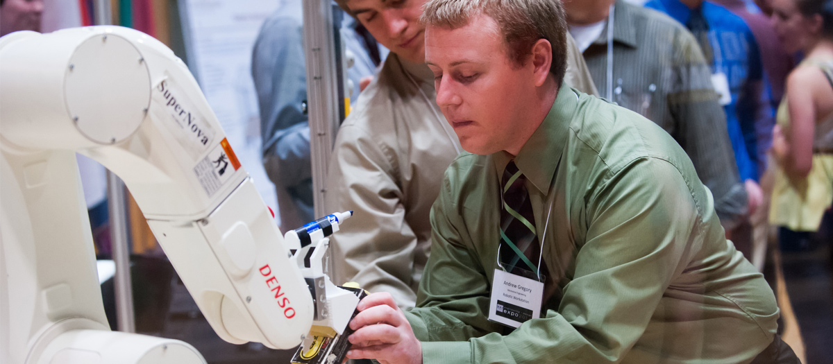 An Engineering EXPO student interacts with a robotic arm