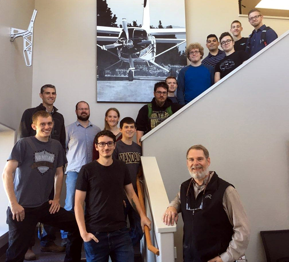 Vandal Engineers assemble in front of a picture of a Kodiak airplane produced by Quest Aircraft.
