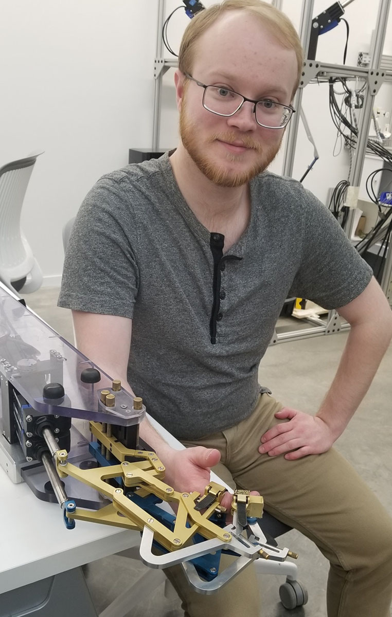 Graduate Student, Marshall Townsend, demonstrates the FINGER robot.