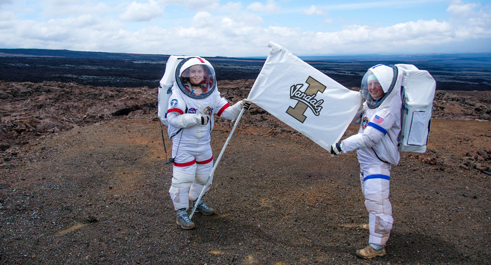 Sophie Milam holds a UI Vandals Flag while wearing the prototype space suit.