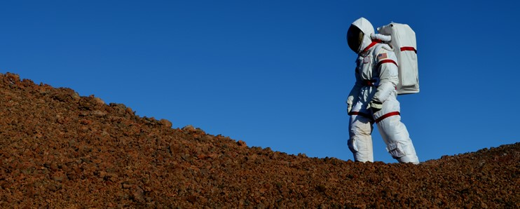 The HI-SEAS space suit walking the rocky landscape.