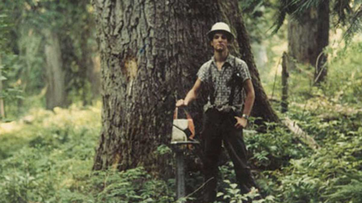 Tom Mueller holding a chainsaw in the forest