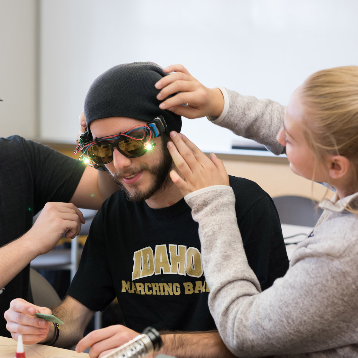 A student wears sunglasses wired with lights