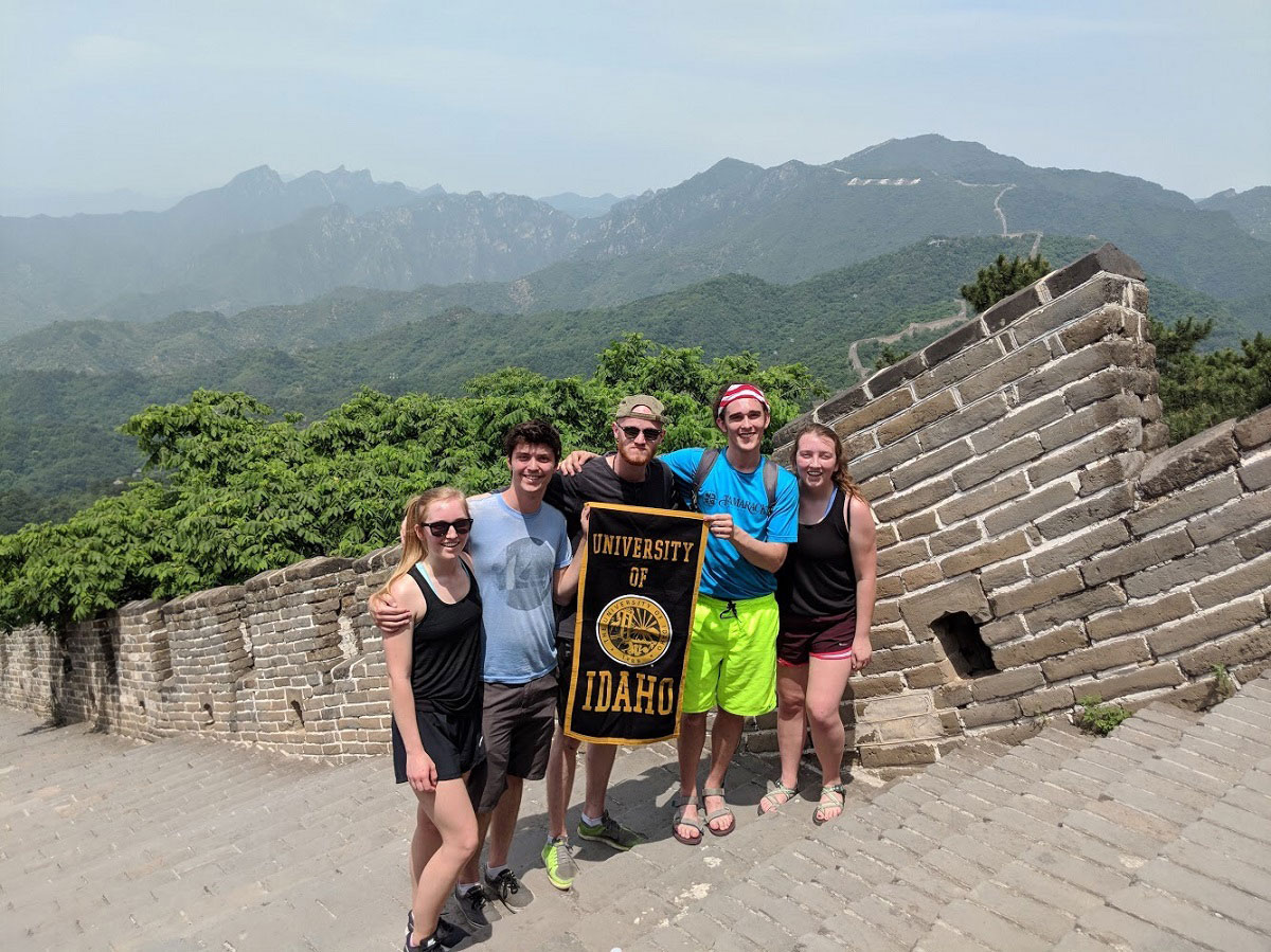 Five engineering students pose with the University of Idaho flag at the Great Wall of China.