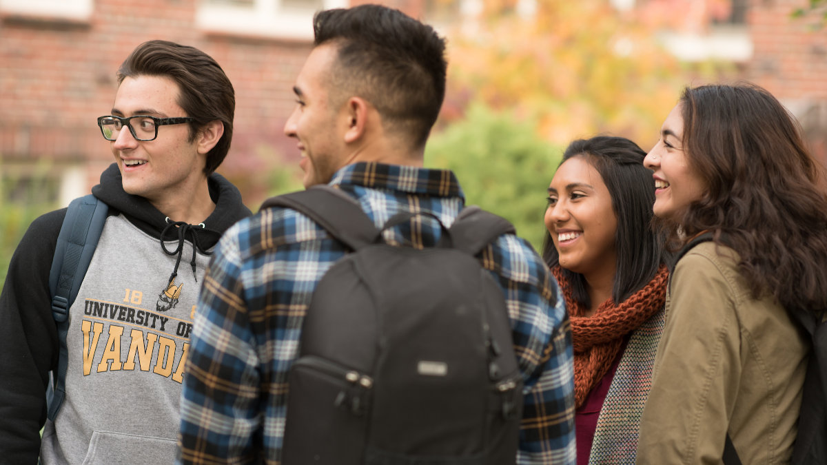Four students laughing outside on campus