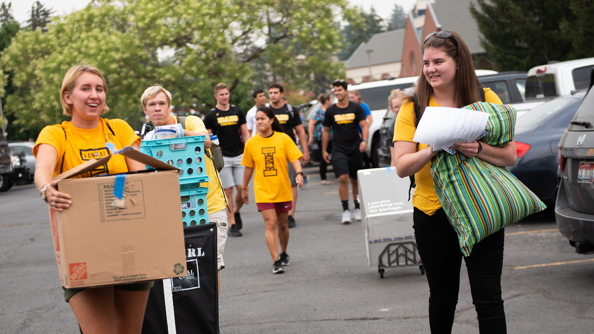 Students, family members and volunteers move boxes, pillows, crates and more into the dorms.