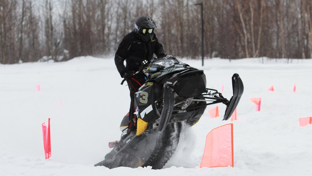 The college of engineering's clean snowmobile takes a jump off from a ramp.