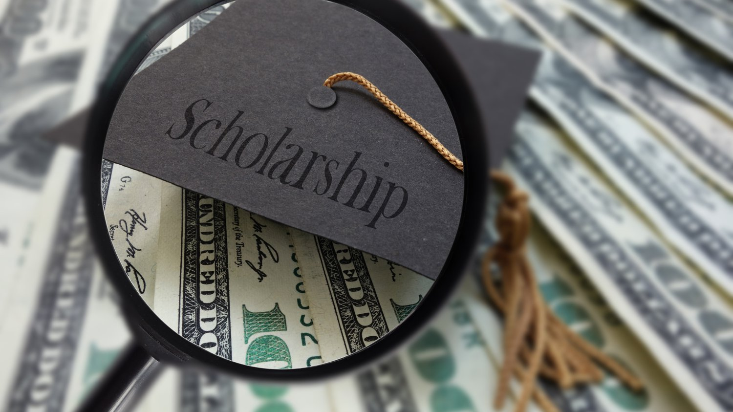 "Stach of US currency and a cap that reads ""scholarships""."