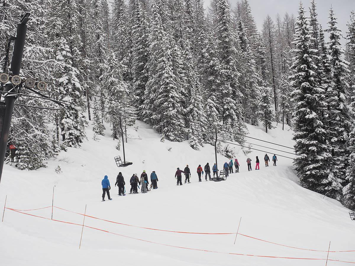 University staff and volunteers teach students how to snow shoe