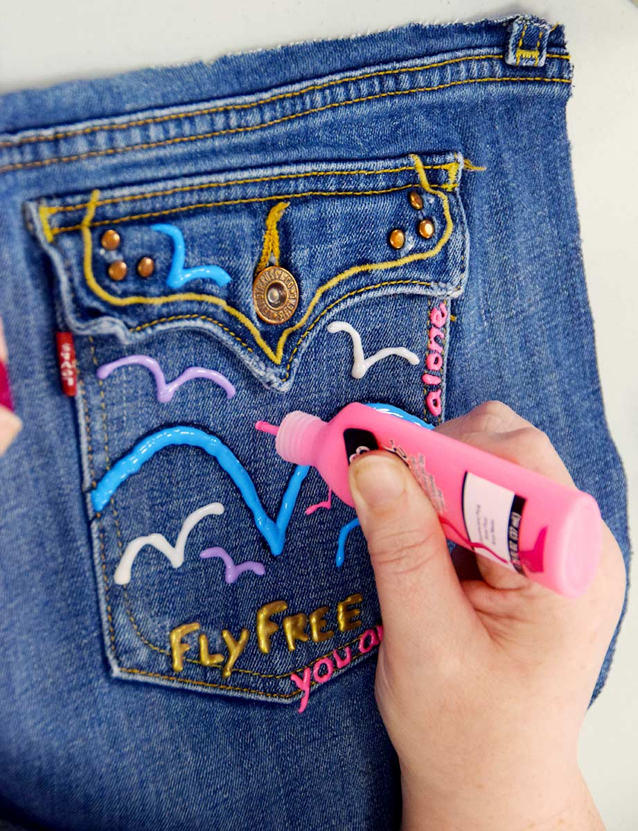 Denim back pocket art using various colors and text fly free on blue