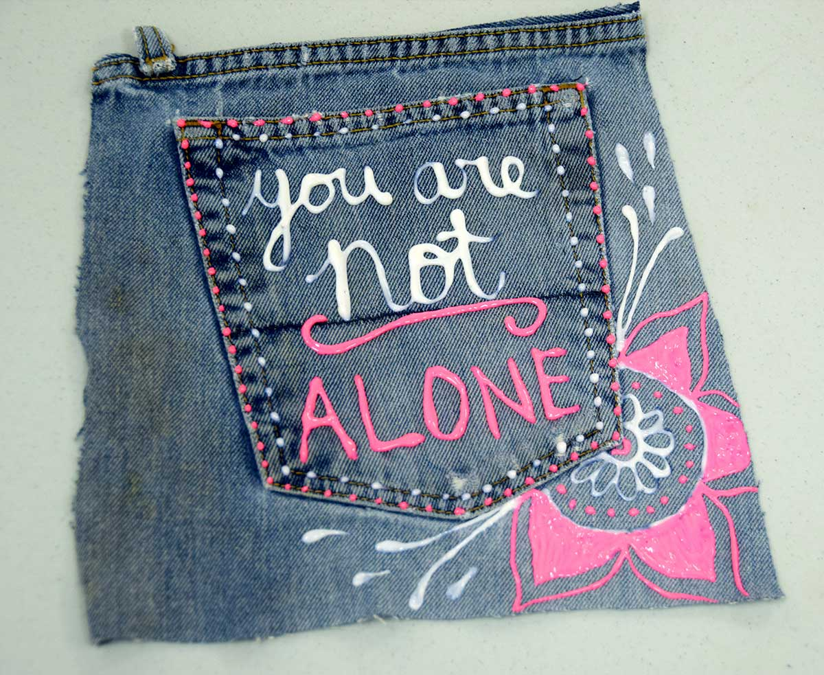 Denim back pocket art using white and pink you are not alone text on blue