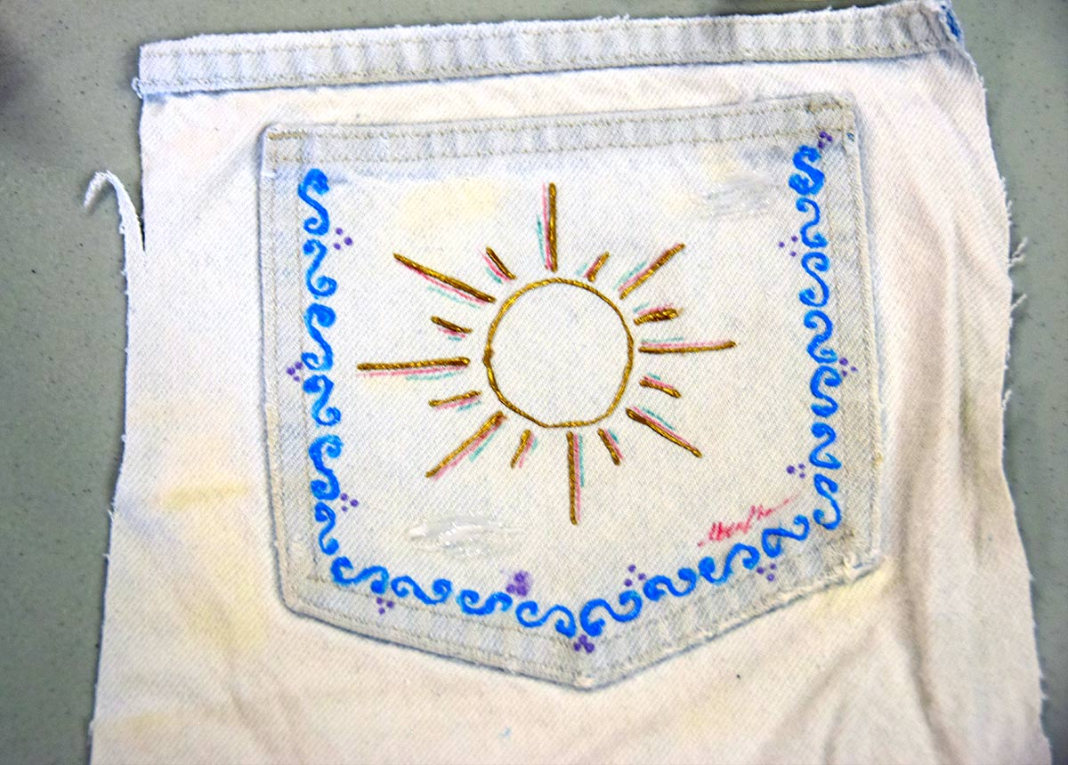 Denim back pocket art using blue and gold on white