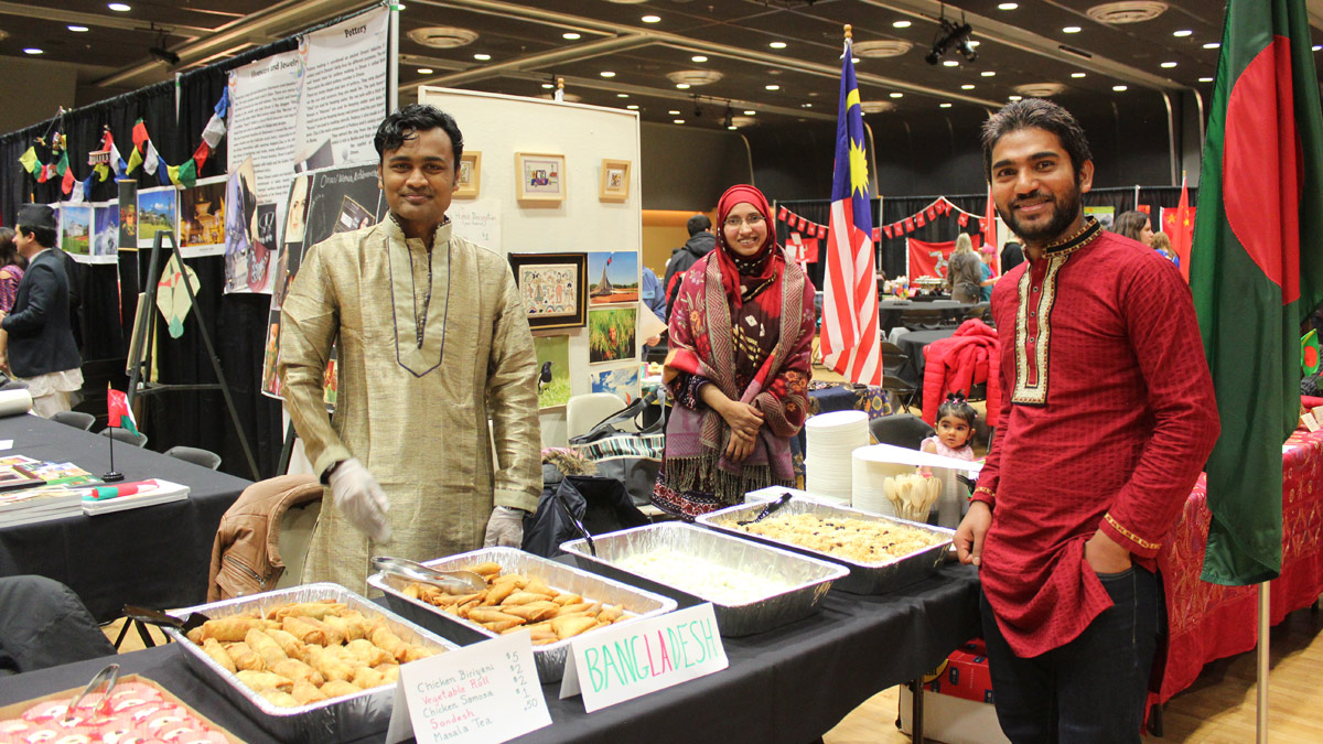 Students pose around a buffet of international cuisine.