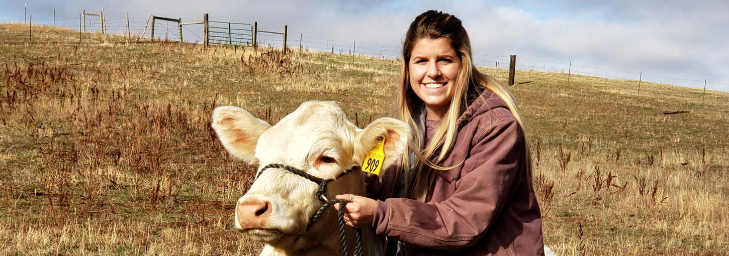 Student Chanelle Brusseau with a cow.