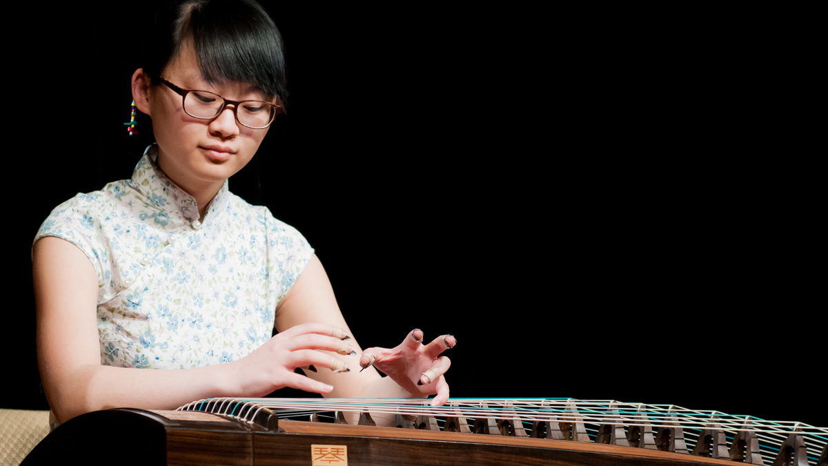 A woman plays an instrument similar to a harpsichord.