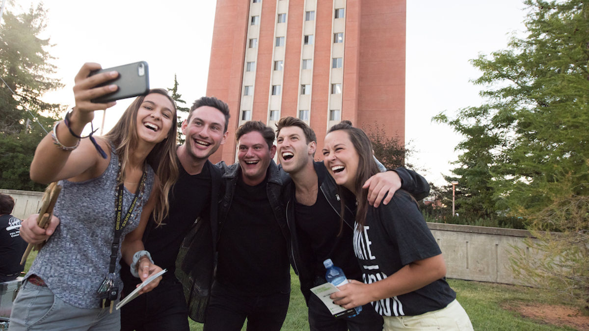 group of students takes a selfie in front of a residence hall