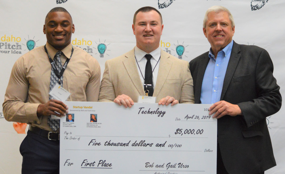 Engineering student Ed Hall and business major Alex Boatman accept Idaho Pitch award.