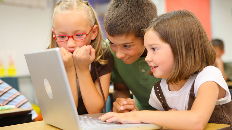 three young students excited about learning from their laptop