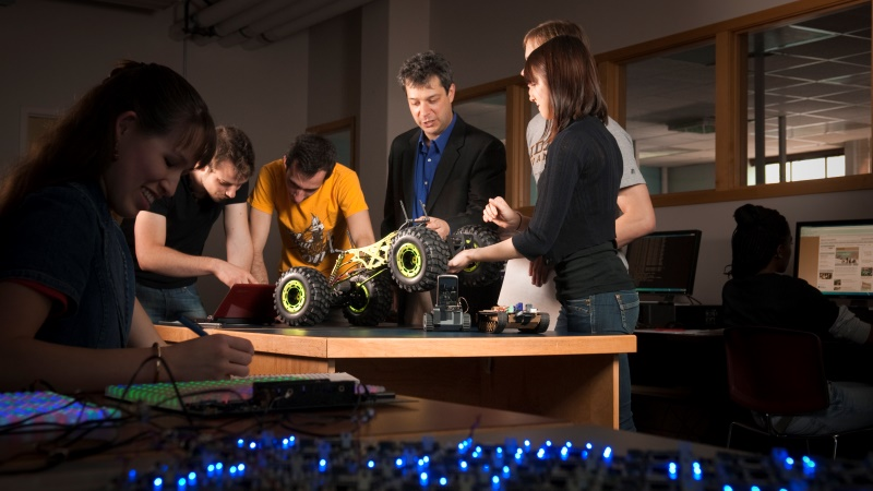 Students working with professor to build a remote controlled car using their newly acquired knowledge from the University of Idaho