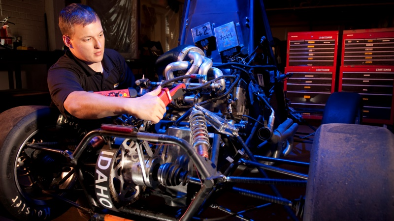 A mechanical engineering student at the University of Idaho works on the engine of a race car, graduate and undergradute students (PhD, Master's and Bachelor's) degree seeking students all work on a number of hands-on projects and competitions.